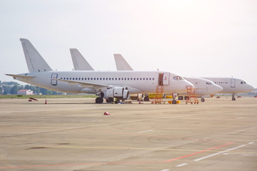 Three different narrow-body aircraft parked at the airport are lined up.