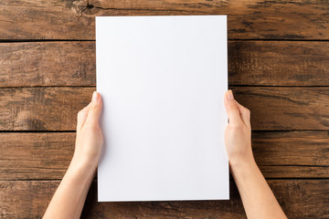 Obraz Overhead shot of woman's hands holding blank paper sheet on rustic wooden table. Close up - fototapety do salonu