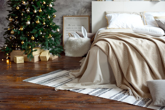 Christmas apartment decor, Scandinavian cozy home decor, bed with warm knitted blankets next to the Christmas tree. Lights and garlands
