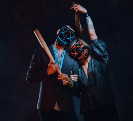 Young family in scary masks are posing for photographer with baseball bat in hands.
