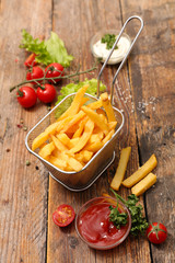 french fries and ketchup on wood background