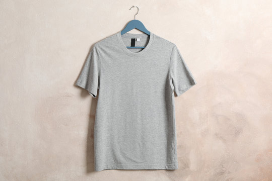 Hanger with blank gray t-shirt on brown background, space for text