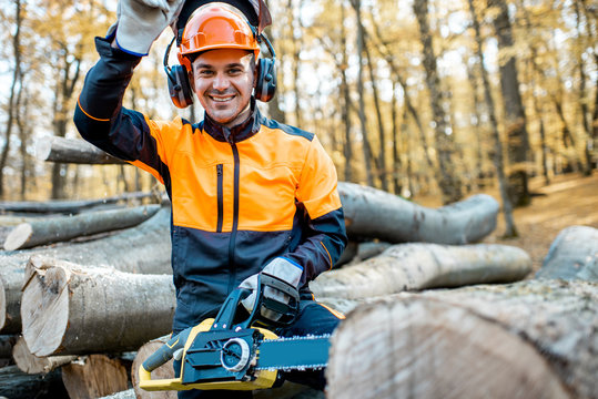 Portrait of a cheerful professional lumberjack in protective workwear standing with a chainsaw on a pile of logs in the forest