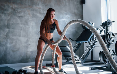 Young fitness woman with slim type of body doing exercises with knots in hands