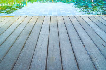 Close up wood floor texture to swimming pool background, perspective view of wooden floor beside swimming pool.