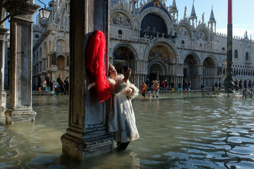 A woman takes pictures in the flooded St. Mark's Square during a period of seasonal high water