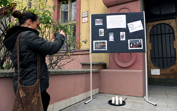 A woman takes a picture of a memorial board for the victims of a bus crash near the city, at the entrance to the secondary vocational school in Nitra
