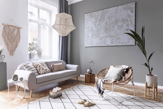 Modern and bohemian composition of interior design with gray sofa, rattan armchair, wooden cube, plaid, pillow, tropical plants, small table and elegant accessories. Stylish home decor. Template.