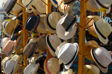 Straw hats for sale at a street market on a sunny afternoon near a lake