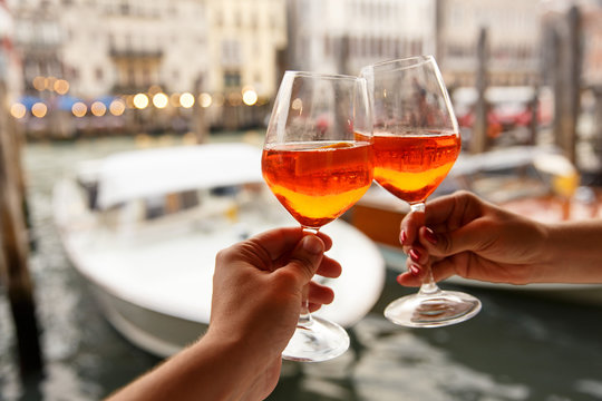 Couple clinking glasses with aperol spritz in Venice, Italy