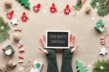 Zero waste Christmas, flat lay, top view on craft paper background with textile doll garland, wrapped gifts, black board with text
