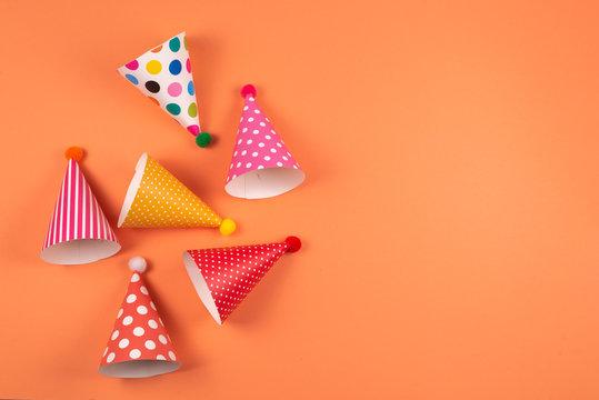 Colorful birthday caps on orange background.