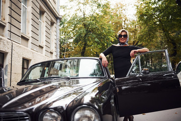 Blonde woman in sunglasses and in black dress near old vintage classic car