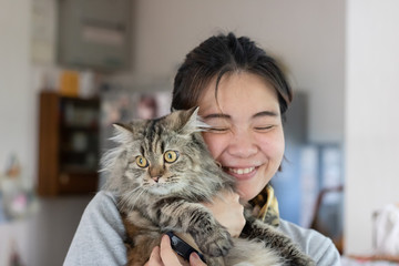 Young Asian woman is hugging a persian cat with indoor scene, human-animal relationships.