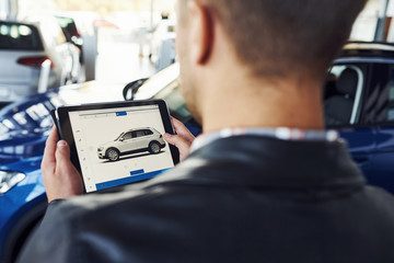 Man stands inside car salon with tablet in hands and looks at the vehicle picture