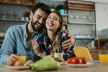 Young cheerful couple having fun during breakfast time in the kitchen. Man is in focus