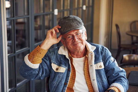 Stylish senior in fashionable clothes and in glasses sits in the cafe and holds hat