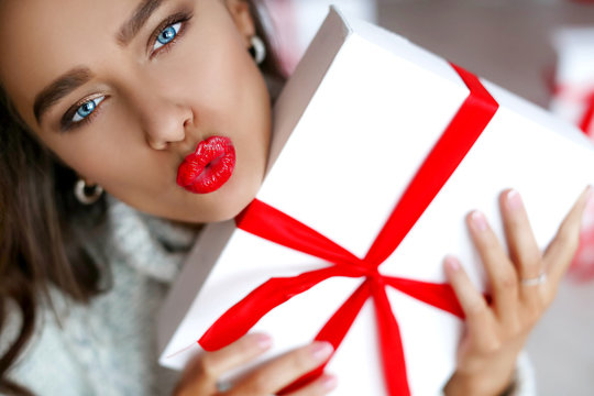 Attractive beautiful and sexy woman with perfect smile and teeth. With makeup at birthday or valentines day holding gift and balloons.