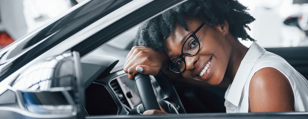 Cheerful smile. Young african american woman sits inside of new modern car