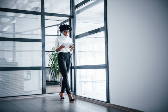 Young african american woman in glasses stands indoors in the office with tablet in hands