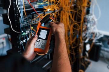 Young man withj measuring device in hands works with internet equipment and wires in server room