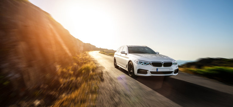 white BMW 5 from 2019 series car in spain mountain landscape road at sunset