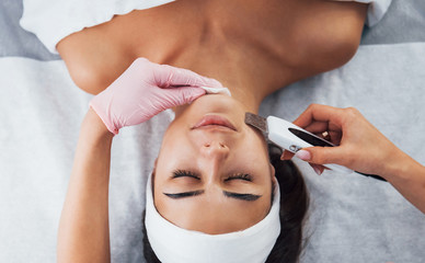 Using special device. Close up view of woman that lying down in spa salon and have face cleaning...