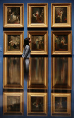 A gallery assistant looks at a collection of portraits of close family members of George IV during a preview of the Royal Collection's George IV: Art & Spectacle exhibition in The Queen's Gallery at Buckingham Palace in London