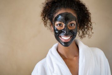 Smiling woman with charcoal face mud Wall mural