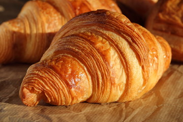 Freshly backed french croissant shiny in the rays of the morning sun  close up Fotomurales