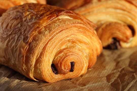Freshly backed french chocolate croissant - petit pain au chocolat shiny in the rays of the morning sun