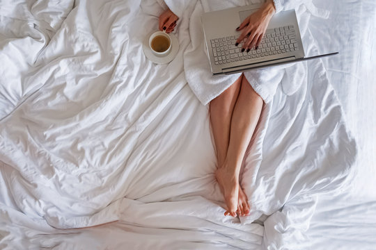 Woman in white bathrobe sitting on the bed with cup of coffee and working on her laptop.