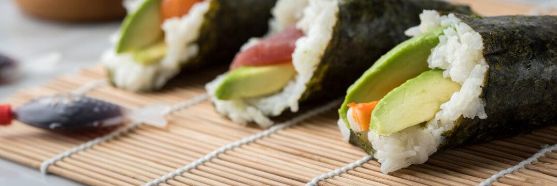 Lachs, Tunfisch und Surimi Avocado Temaki Sushi, eingelegter Ingwer mit Soja Soße Fische und Sushimatte auf Marmor Hintergrund