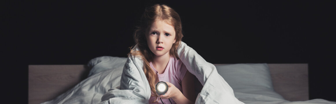 panoramic shot of scared child sitting on bedding and holding flashlight isolated on black