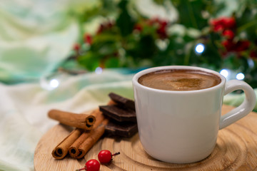 Cup of espresso next to cinnamon sticks and dark chocolate in a festive decor. Christmas morning coffee.