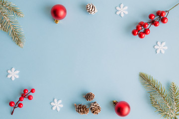 Christmas frame made of fir branches, red berries, snowflakes, bauble decoration and pine cones on blue background. Christmas background. Flat lay. Top view with copy space