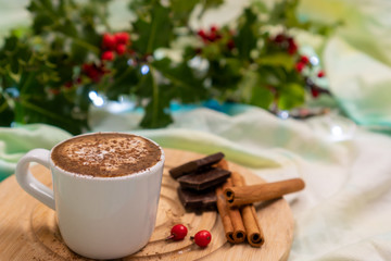 Cup of cappuccino next to cinnamon sticks and dark chocolate in a festive decor. Christmas morning coffee.