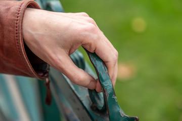 Detail of female hand holding metal door in garden