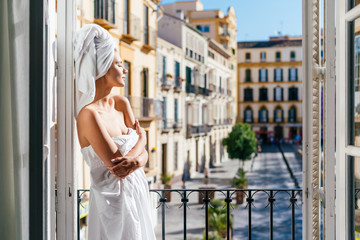 tourist girl in the hotel, after a shower stands by the open balcony enjoying the sunshine, covering her eyes