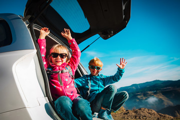 happy kids- boy and girl- travel by car in mountains