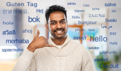 emotion, expression and people concept - smiling indian man in knitted woolen sweater making phone call gesture over greeting words in different foreign languages