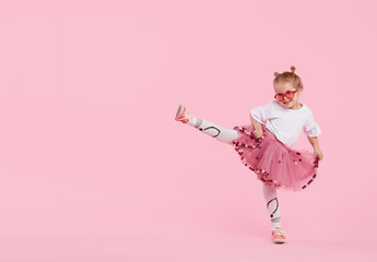 Spoed Fotobehang Carnaval Happy childhood. Funny child girl in tulle skirt jumping and having fun isolated on pink background. Celebrating a vibrant carnival for kids, birthday party. True emotions. Space for text