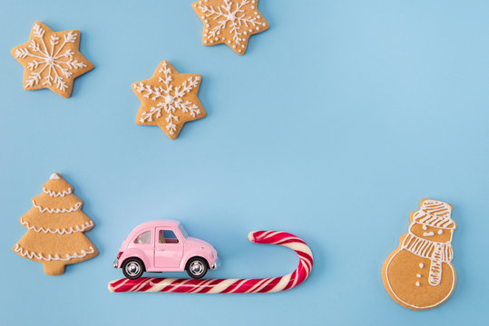 High angle view photo of x-mas greeting postcard small retro pink car driving home on candy stick newyear night decor cookies figures fir tree stars isolated blue color background