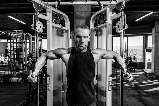 Young strong sweaty focused fit muscular bodybuilder man chest stretching workout on cable machine in the gym  for strength and good looking of muscles training black and white