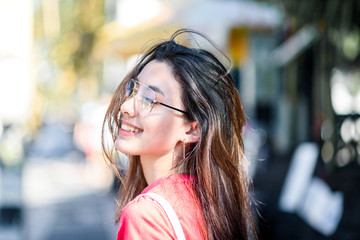 Young asian beautiful female smiling walking on city street at sunset time