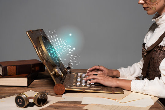 cropped view of woman typing on steampunk laptop with glowing digital illustration at table isolated on grey