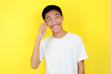 Portrait of smart and happy young Asian man thinking and look up. Happy young Asian man wearing white t-shirt thinking and look up