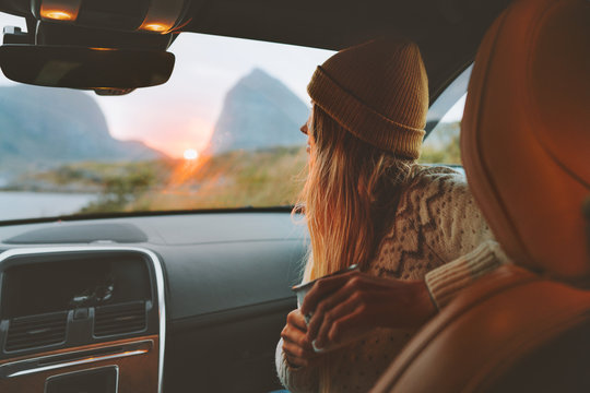 Woman on road trip traveling by rental car relaxing with coffee cup adventure lifestyle vacations vibes outdoor sunset Norway mountains view in window