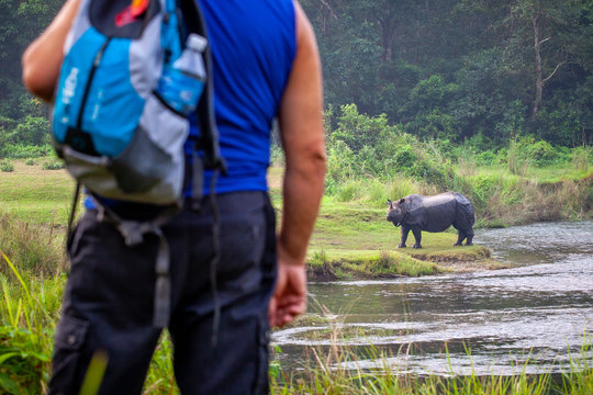 A tourist watching a wild Rhinoceros during a walking safari in the Chitwan national park, Nepal
