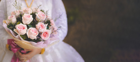 A bouquet of roses in the bride's hand